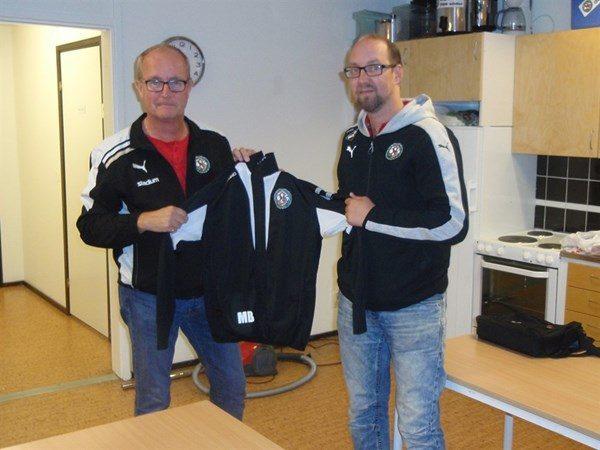 ÖSK Söders Tommy Sandberg kollar passformen på Mikael Bjälkefors nya tränarjacka. Den kommer nog att sitta bra.